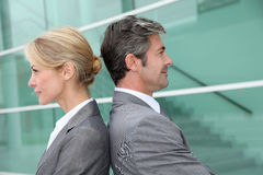 Business people standing back to back and smiling Royalty Free Stock Photo