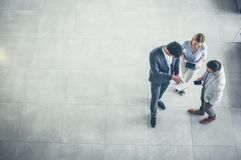 Business people standing in business building and having conversation. Copy space. stock photography
