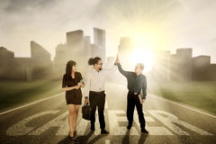 Business people standing on the career word. Group of diversity business people giving high five while standing on the road with word of career Stock Photos