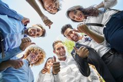 Business people standing in circle showing thumbs up stock photography