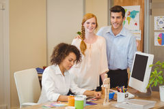 Business people standing by colleague working at desk Royalty Free Stock Photos