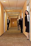 Business people standing in corridor Stock Images