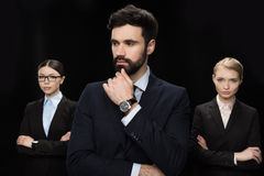 Business people standing with crossed arms isolated on black, business establishment concept. Pensive business people standing with crossed arms isolated on stock images