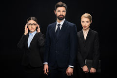 Business people standing with crossed arms isolated on black. Team building concept Royalty Free Stock Images