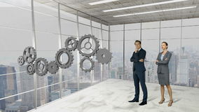 Business people standing in front of gear-wheels. In a business environment stock video footage
