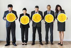Business people standing and holding currency icons Stock Image