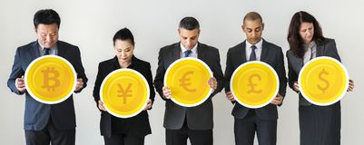 Business people standing and holding currency icons Stock Photos