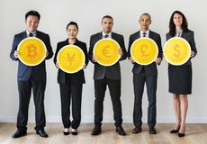 Business people standing and holding currency icons Royalty Free Stock Image