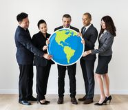 Business people standing and holding globe icon Stock Photo