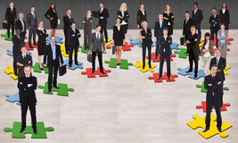 Business people standing on jigsaw pieces. Group of multi ethnic business people standing on jigsaw pieces Royalty Free Stock Images