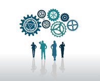 Business people standing with large cogs and wheels Royalty Free Stock Image