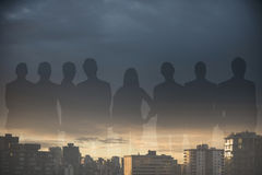 Composite image of business people standing over white background. Business people standing over white background against city against cloudy sky during sunset Royalty Free Stock Images