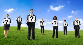 Business people standing at the park and holding the questions mark sign Stock Photos