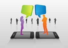 Business people standing on smartphones with speech bubbles Royalty Free Stock Image