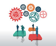 Business people standing on speech bubbles with large cogs and wheels Royalty Free Stock Images