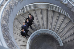 Business People Standing On Spiral Staircase. High angle portrait of multiethnic business people standing on spiral staircase Stock Photography