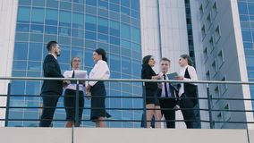 Business people standing on a terrace in front of the business center stock footage