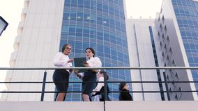 Business people standing on terrace of office building in the center of city and doing their business. Two women are talking to each other and a man is busy on stock video