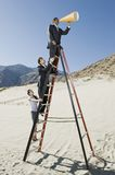 Business People on Stepladder Using Megaphone in Desert Stock Photo