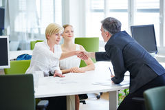 Business people at table shaking Stock Image