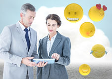 Business people with tablet against cloud and ground with emojis Stock Images