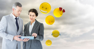 Business people with tablet against cloudy sky with emojis Stock Photos