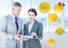 Business people with tablet against window and emojis Stock Photography