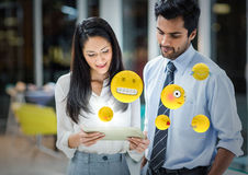 Business people with tablet and emojis with flares in blurry office. Digital composite of Business people with tablet and emojis with flares in blurry office Royalty Free Stock Photography