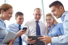 Business people with tablet pc and smartphones. Business, teamwork, people and technology concept - business team with tablet pc and smartphones meeting in Stock Photography
