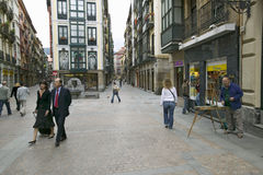 Business people take lunchtime walk as painter paints in Bilbao (Bilbo), the North Coast of Spain Stock Images