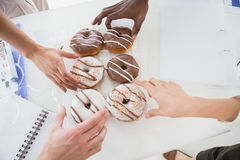Business people taking doughnut at desk. In the office Royalty Free Stock Photos