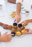Business people taking muffins from plate Royalty Free Stock Images