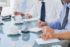 Business people taking notes on notepads Royalty Free Stock Image