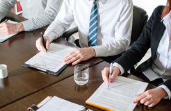 Business people taking notes Royalty Free Stock Photography