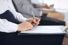 Business people taking part at conference or training at office, close-up. Women sitting on chairs and making notes like. At queue or meeting stock photo