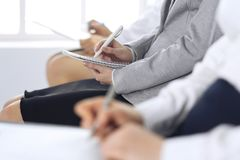 Business people taking part at conference or training at office, close-up. Women sitting on chairs and making notes like. At queue or meeting stock photography