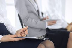 Business people taking part at conference or training at office, close-up. Women sitting on chairs and making notes like. At queue or meeting stock photos