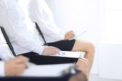 Business people taking part at conference or training at office, close-up. Women sitting on chairs and making notes like. At queue or meeting royalty free stock image