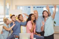 Business people taking selfie in meeting room Royalty Free Stock Image