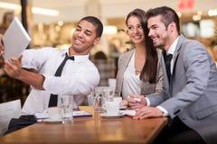 Business people taking selfie in restaurant Stock Photo