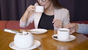 Business people talk and drink coffee while sitting in restaurant. stock footage
