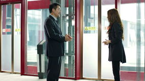 Business people talking in elevator hall. Two business people talking in elevator area, happy and smiling stock video