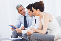 Business people talking about files on sofa Royalty Free Stock Image