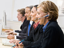 Business people talking on headsets. At computers Royalty Free Stock Photography