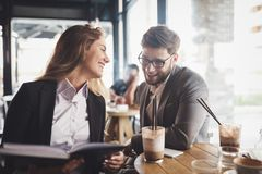Business people talking and laughing together. At cafe stock image