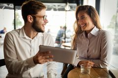 Business people talking and laughing together. At cafe royalty free stock image