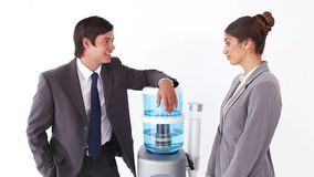 Business people talking next to the water cooler. Against a white background stock video