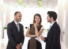 Business people talking in office corridor stock photography