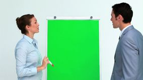 Business people talking and pointing a board. In studio stock footage