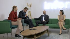 Business people talking and sitting on couches. Four business people sitting on couches and talking, friendly conversation, smile, two women and two men, relaxed stock footage